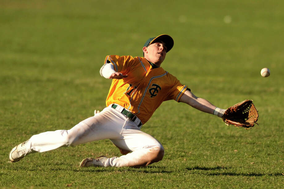 Trinity Catholic right fielder Matt Christensen misses a fly ball during the Crusaders' baseball game against Stratford at Trinity Catholic High School in Stamford, Conn., on Wednesday, April 9, 2014. Trinity Catholic won, 4-2. Photo: Jason Rearick / Stamford Advocate