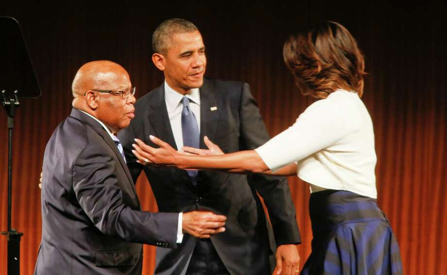 U.S. Rep. John Lewis of Georgia, left, is greeted by President Barack Obama, center, and his wife, Michelle, before a keynote address during the Civil Rights Summit on Thursday, April 10, 2014, in Austin, Texas. (AP Photo/Jack Plunkett) Photo: Jack Plunkett, Associated Press / FR59553 AP