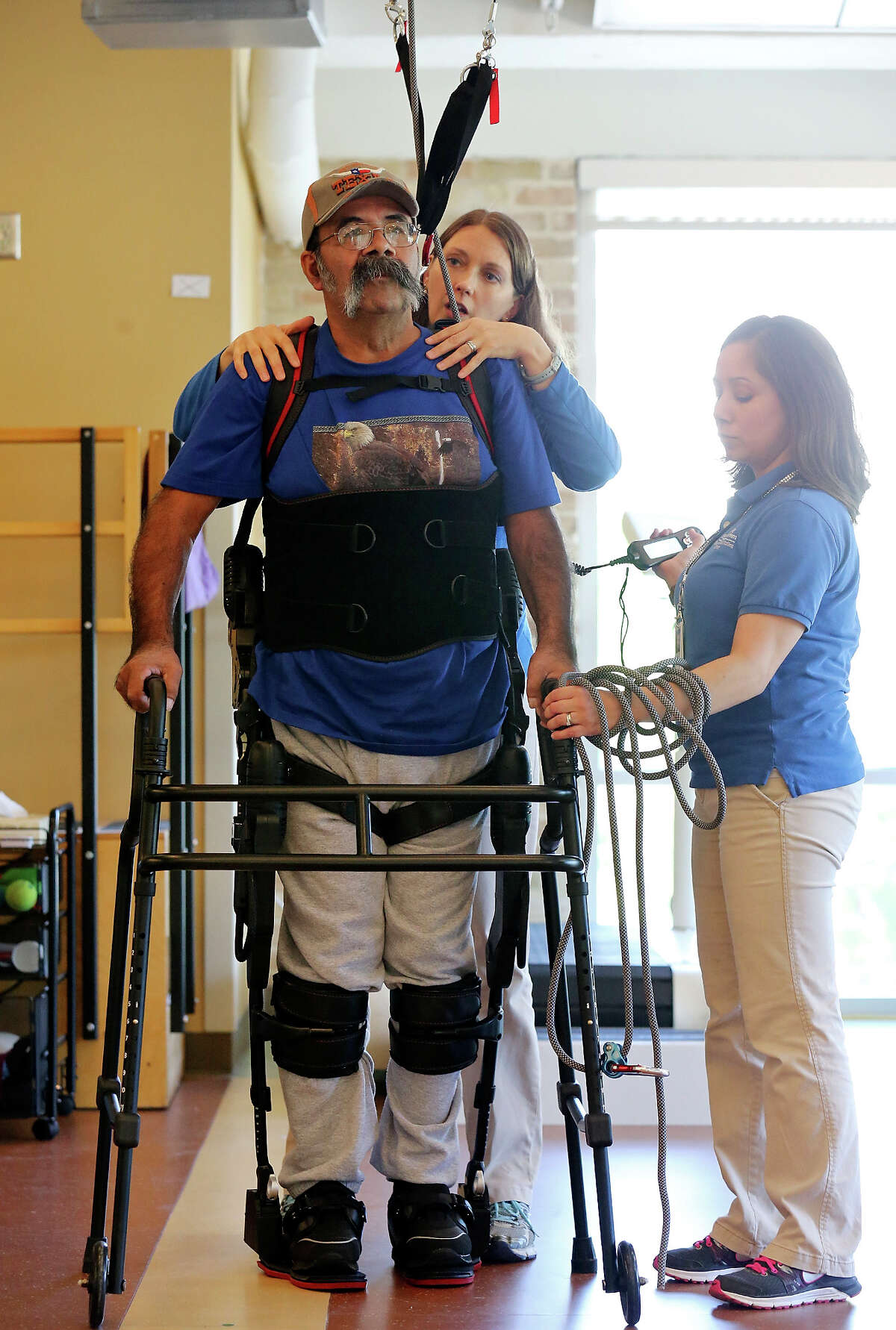 Physical therapists Chara Rodriguez (left) and Julietta Douglas (right) work with Pedro Lozano, 56 while he wears a Ekso exoskeleton suit to help him walk, during therapy Thursday April 10, 2014 at the University Health System's Reeves Rehabilitation Center. Lozano is paralyzed on his left side after suffering a stroke Dec. 27, 2013.