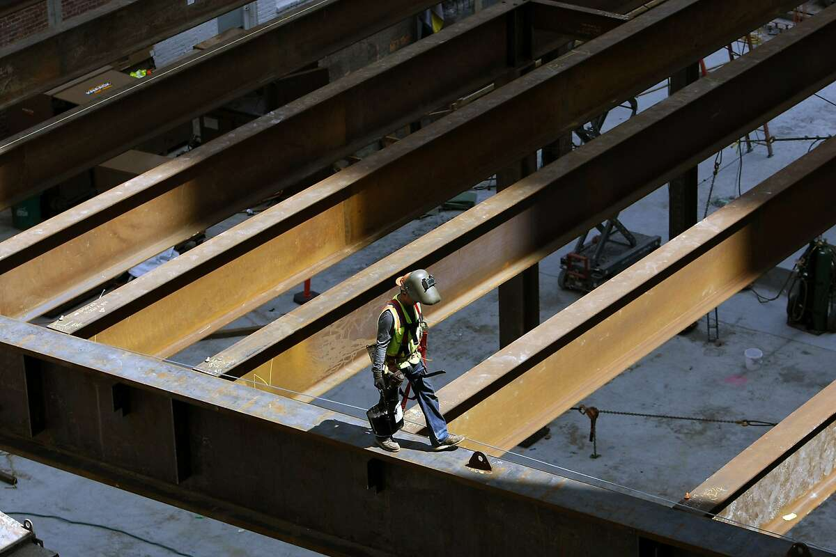 A worker with SME Steel works on top of the first steel sections to be erected as construction continues at the San Francisco Museum of Modern Art in San Francisco, CA, Tuesday April 8, 2014.