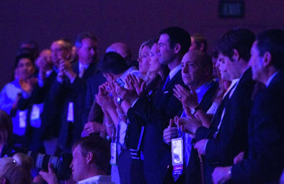 Members of the audience give a standing ovation as former U.S. Secretary of State Hillary Rodham Clinton continues with her speech after an object was thrown on stage during her address to members of the Institute of Scrap Recycling Industries during their annual convention at the Mandalay Bay Convention Center, Thursday, April 10, 2014, in Las Vegas. Clinton, a possible presidential contender in 2016, ducked but did not appear to be hit by the object, and then joked about the incident. Security ushered out a woman who said she threw a shoe but didn't identify herself to reporters or explain the action.  LAS VEGAS REVIEW-JOURNAL OUT Photo: Steve Marcus, AP / Las Vegas Sun