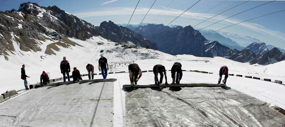 FILE - In this May 10, 2011 file photo, workers cover the glacier with oversized plastic sheets on the peak of Germany's highest mountain Zugspitze (2962 meters) near Garmisch-Partenkirchen, southern Germany. The sheets are meant to keep the glacier from melting during the summer months. It's Plan B in the fight against climate change: cooling the planet by sucking heat-trapping CO2 from the air or reflecting sunlight back into space. The U.N.'s expert panel on climate change is under pressure from both sides this week in Berlin, Germany, as it considers whether geoengineering should be part of the toolkit that governments use to keep global warming in check. (AP Photo/Matthias Schrader, File) ORG XMIT: LGL103 Photo: Matthias Schrader / AP