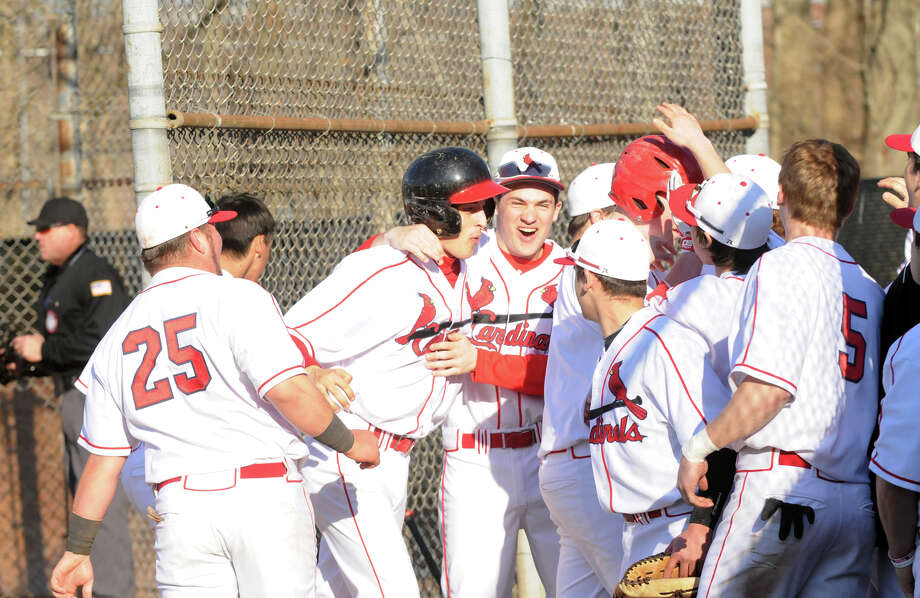 J.T. Hintzen, center left, is greeted by teammates after hitting a home run as Greenwich High School hosts Daniel Hand in a baseball game in Greenwich, Conn., April 10, 2014. Greenwich won the game 7-5. Photo: Keelin Daly / Stamford Advocate Freelance