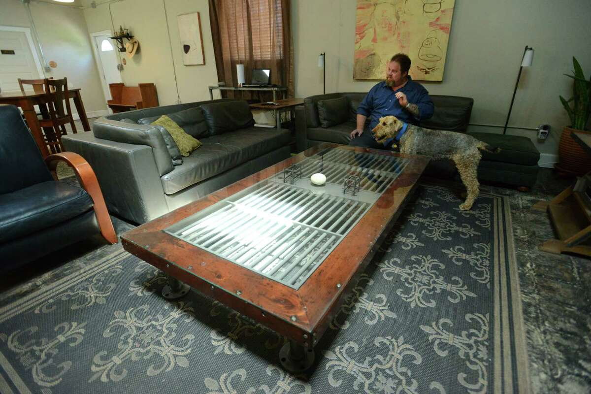 Gordon Wise sits with a rescued airedale terrier in his spacious apartment in an industrial building that was once a meat processing plant. Wise has turned a portion of the building into a haunted house, another portion into a talking board museum and is also in the process of having 16 apartments built inside of the structure. Thursday, April 10, 2014. The large coffee table was once a jail cell door.