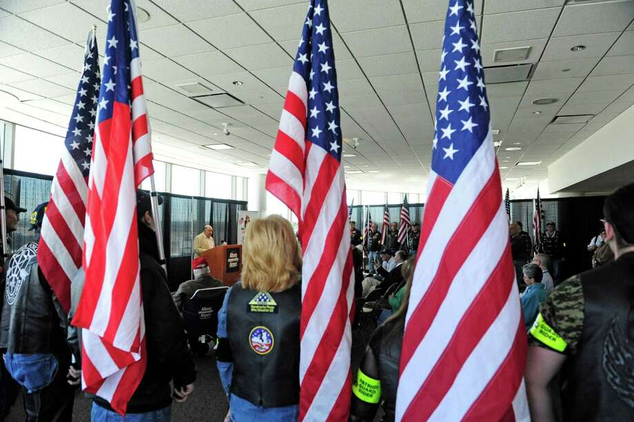 Members of the Patriot Guard Riders hold flags as Frank DeSorbo, background left at podium, president of Patriot Flight Inc. addresses those gathered for a press event at the Albany International Airport on Thursday, April 10, 2014, in Colonie, N.Y.  Albanya€™s Patriot Flight Inc. held the event to announce a special 70th Anniversary of D-Day Flight is scheduled for May 10, 2014.  The flight will take 57 veterans to Washington D.C. to see their respected war memorial.  (Paul Buckowski / Times Union) Photo: Paul Buckowski / 00026407A