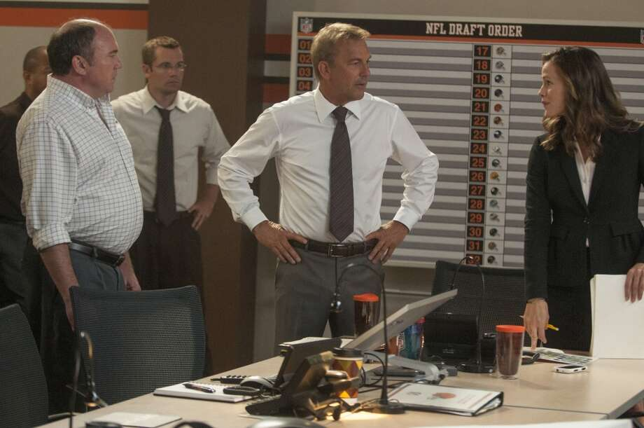 "Kevin Costner, center, and Jennifer Garner, right, in a scene from ""Draft Day."" Photo: Dale Robinette, Associated Press"