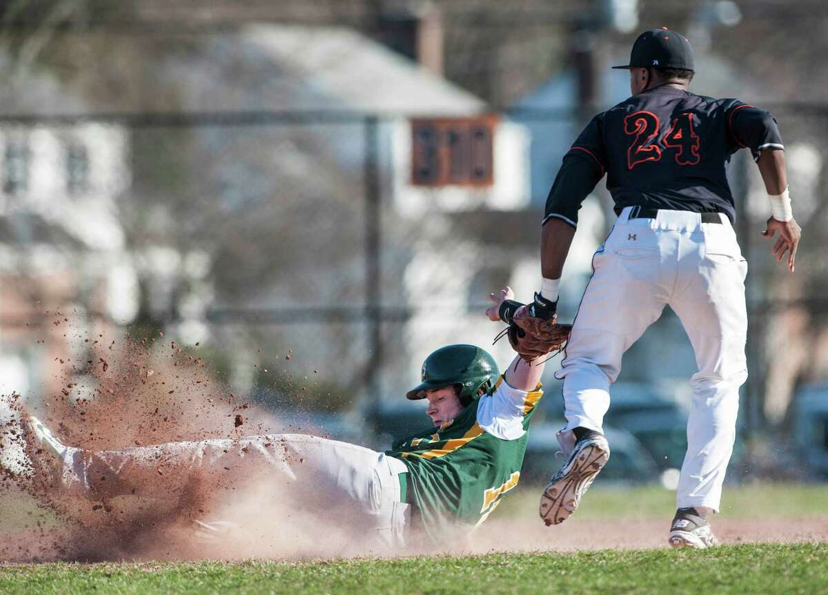 Stamford high school shortstop Kenny Wright tags Trinity Catholic high school's Thomas Costigan out as he slides into second base during a baseball game played at Stamford high school, Stamford, CT on Thursday, April, 10th, 2014.