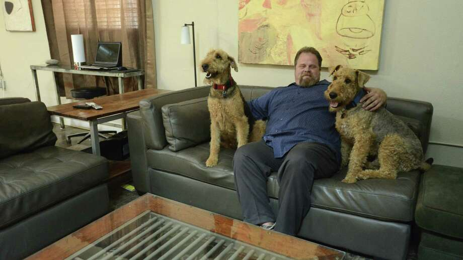 Gordon Wise relaxes with a pair of rescued dogs in his spacious apartment in an old industrial building near the AT&T Center that was once a meat processing plant. Wise was co-owner of the defunct Nightmare on Grayson haunted house near the Pearl. Photo: Photos By Billy Calzada / San Antonio Express-News / San Antonio Express-News