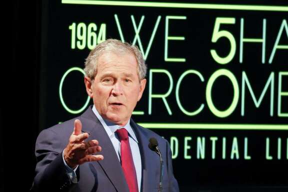 Former President George W. Bush motions towards his wife, Laura, while giving an address during the Civil Rights Summit on Thursday, April 10, 2014, in Austin, Texas. (AP Photo/Jack Plunkett)