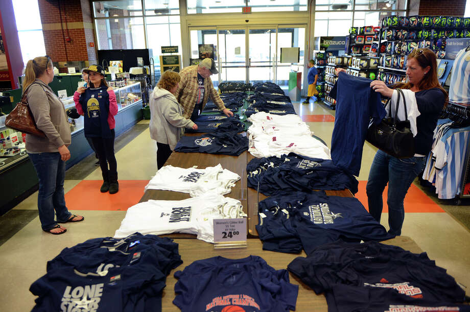People browse the UConn merchandise table at Dick's Sporting Goods at the Connecticut Post Mall in Milford, Conn. on Thursday April 10, 2014. The UConn men and women basketball teams both won their Final Four championships and people are rushing out to purchase sports memorabilia like this. Photo: Christian Abraham / Connecticut Post