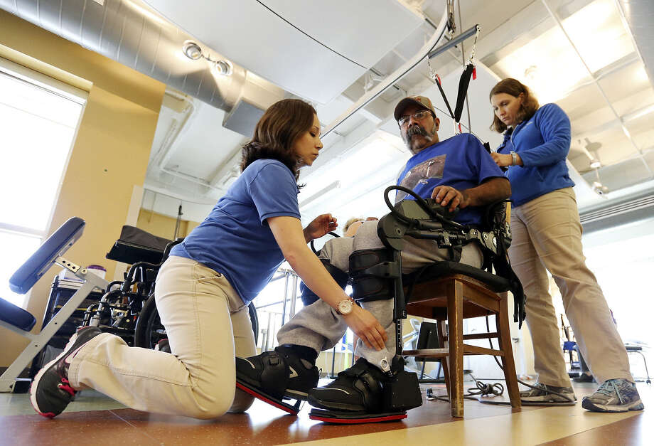 Julietta Douglas (left) and Chara Rodriguez get Pedro Lozano ready for therapy. After his hour-long physical therapy session in which he walked almost 500 steps, Lozano said the Ekso exoskeleton is not difficult to use. Photo: Edward A. Ornelas / San Antonio Express-News / © 2014 San Antonio Express-News