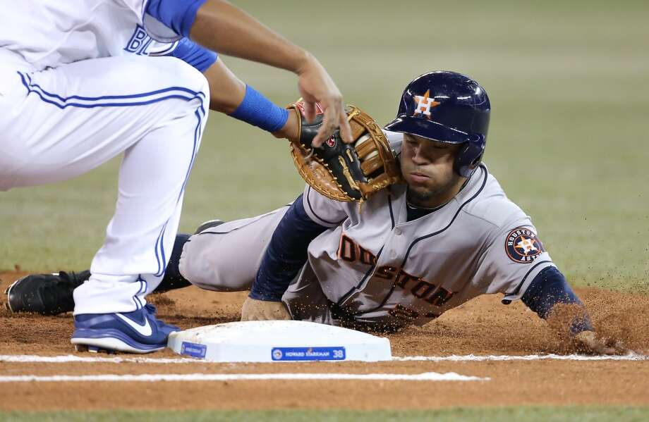 Jose Altuve of the Astros is picked off first base by Edwin Encarnacion. Photo: Tom Szczerbowski, Getty Images