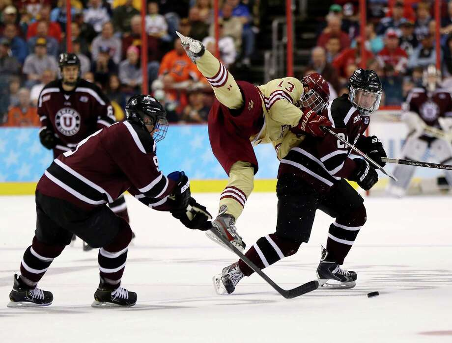 PHILADELPHIA, PA - APRIL 10:  Johnny Gaudreau #13 of the Boston College Eagles collides with Mike Vecchione #21 of the Union College Dutchmen as Daniel Carr #99 of the Dutchmen plays the puck during the 2014 NCAA Division I Men's Hockey Championship Semifinal at Wells Fargo Center on April 10, 2014 in Philadelphia, Pennsylvania.  (Photo by Elsa/Getty Images) ORG XMIT: 464911393 Photo: Elsa / 2014 Getty Images