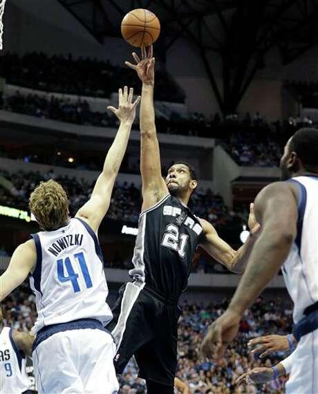 San Antonio Spurs forward Tim Duncan (21) shoots against Dallas Mavericks forward Dirk Nowitzki (41) of Germany during the first half an NBA basketball game Thursday, April 10, 2014, in Dallas. (AP Photo/LM Otero) Photo: LM Otero, AP / AP