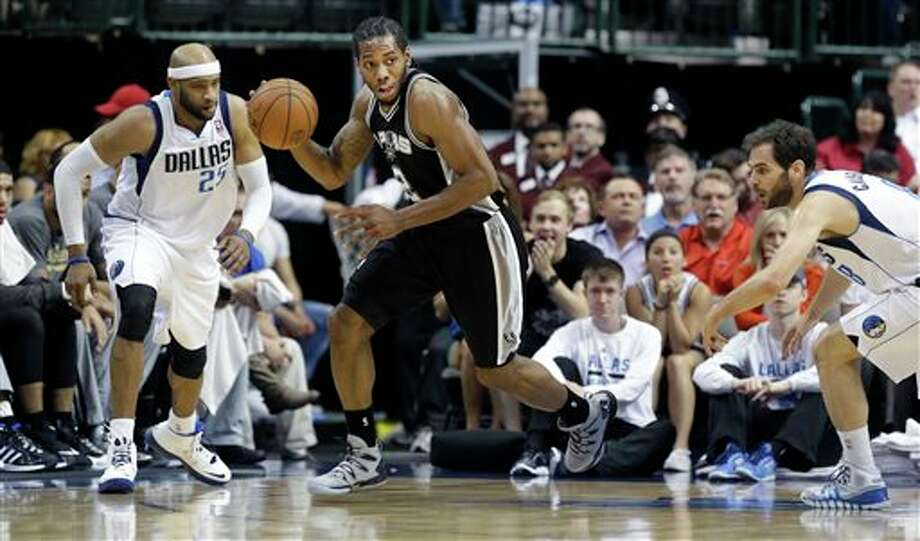 San Antonio Spurs forward Kawhi Leonard (2) comes up with a loose ball against Dallas Mavericks guard Jose Calderon, right, and guard Vince Carter during the first half an NBA basketball game Thursday, April 10, 2014, in Dallas. (AP Photo/LM Otero) Photo: LM Otero, AP / AP