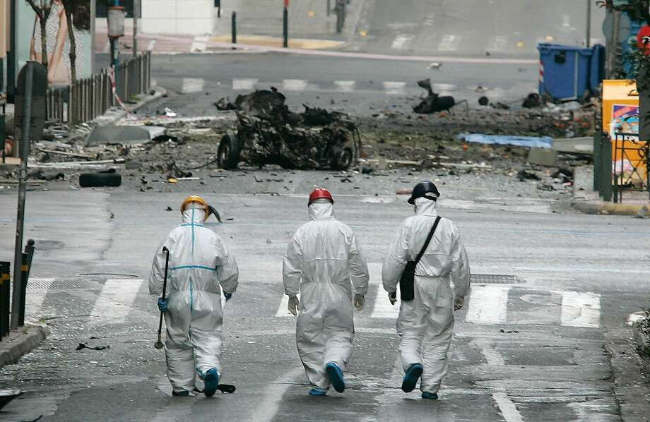 ATHENS, GREECE - APRIL 10:  Forensic police examine the scene after a car bomb explosion in central Athens on April 10, 2014 in Athens, Greece. The bomb exploded outside a Bank of Greece building in central Athens before dawn Thursday, causing some damage but no injuries. The blast came hours before Greece was to return to the international bond markets for the first time in four years, and a day before German Chancellor Angela Merkel was to visit Athens. (Photo by Milos Bicanski /Getty Images) *** BESTPIX *** Photo: Milos Bicanski, Getty Images