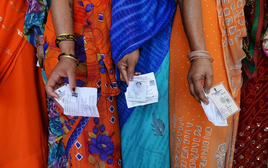 TOPSHOTS Indian voters pose with their voting slips as they stand in a line to cast their vote outside a polling station at Dabua village on the outskirts of Faridabad on April 10, 2014, during the third stage of voting for national elections in the northern state of Haryana. India's upstart anti-graft party faced a key test as the national capital voted in the first major phase of the country's marathon general elections. The third phase of voting began at 7:00 am (0130 GMT) in 91 constituencies, representing nearly a fifth of the 543-seat lower house, across the capital and 13 other states, including Maoist insurgency-hit eastern India.AFP PHOTO/ SAJJAD HUSSAINSAJJAD HUSSAIN/AFP/Getty Images Photo: Sajjad Hussain, AFP/Getty Images