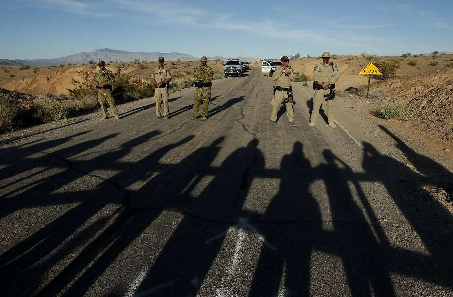 Federal law enforcement officers block a road at the Lake Mead National Recreation Area near Overton, Nev. Thursday, April 10, 2014. In the foreground are the shadows of protestors. Two people were detained while protesting the roundup of cattle owned by Cliven Bundy on the road. (AP Photo/Las Vegas Review-Journal, John Locher) Photo: John Locher, Associated Press
