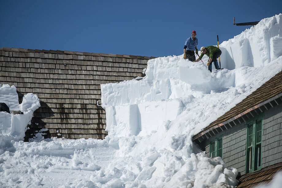 After carving a large block of snow off the roof of the Paradise Inn, maintenance workers, Jonathan Lawton, left, and his brother, Daniel Lawton, toss the icy block down the snow bank as the clear the hotel's roof on Thursday, April 10, 2014 at the Paradise area of Mount Rainier National Park. The road between Longmire and Paradise at the national park is now open over night. The Paradise Inn plans to open its doors May 21, 2014. (AP Photo/The Chronicle, Pete Caster) Photo: Pete Caster, Associated Press