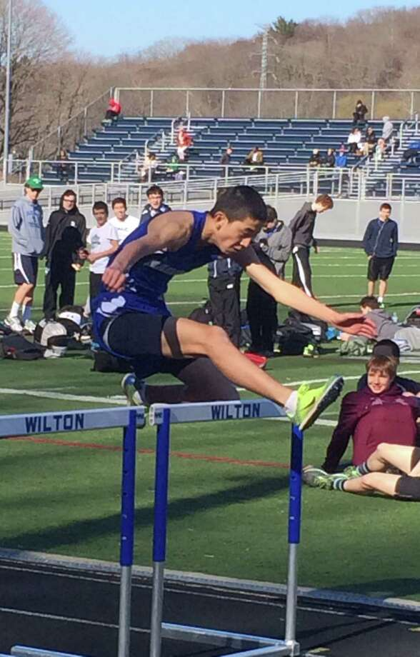 Kenny Yamaguchi leaps over the final hurdle of the 110m hurdle dash during Darien's opening meet of 2014 at Wilton on Thursday, April 10. Photo: Andrew Callahan / Darien News