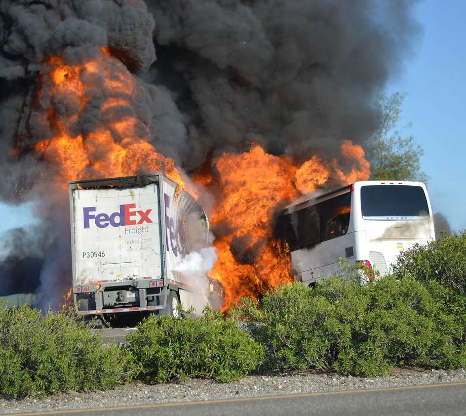 Massive flames are seen devouring both vehicles just after the crash, and clouds of smoke billowed into the sky  Thursday April 10, 2014 until firefighters had quenched the fire, leaving behind scorched black hulks of metal. The FedEx tractor-trailer crossed a grassy freeway median in Northern California and slammed into the bus carrying high school students on a visit to a college. At least nine were killed in the fiery crash, authorities said. (AP Photo/Jeremy Lockett) Photo: Jeremy Lockett, Associated Press