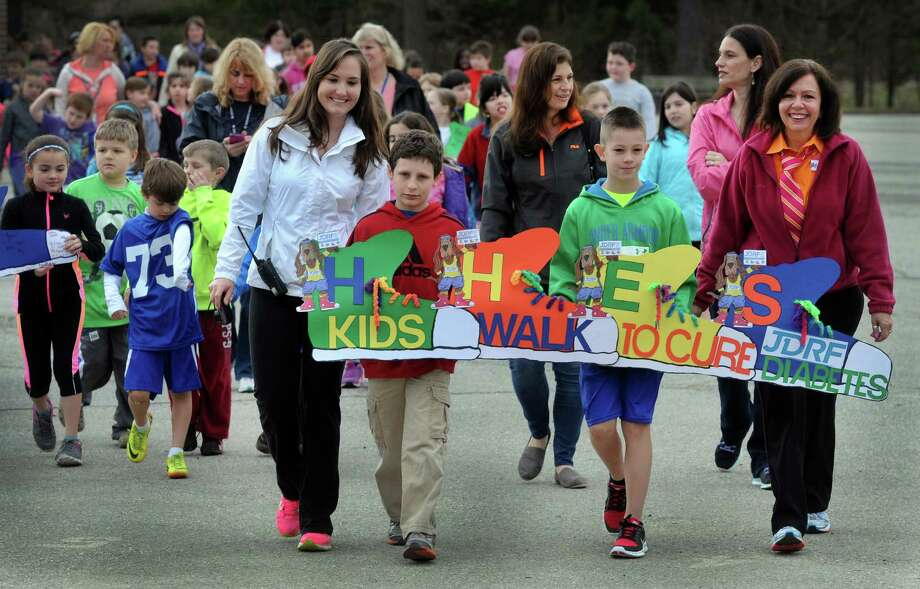 Huckleberry Hill Elementary School students and staff participate in the annual JDRF Kids Walk for Diabetes Friday morning, April 11, 2014 in Brookfield, Conn. Top fundraisers Aidan Sarmiere, left, and Kyle Rosa, 9, both children with diabetes, along with school nurse Monica Walsh, right, lead about 700 students and staff around the school building three times Friday morning, April 11, 2014, as part of the school's annual fundraiser to benefit Juvenile Diabetes research. The third annual walk at Huckleberry raised over $6500. Photo: Carol Kaliff / The News-Times