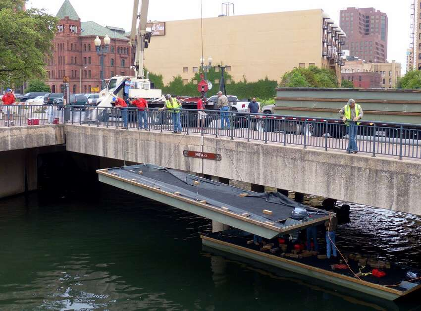 Workers lower a barge into the San Antonio River on Friday, April 11, 2014, during the annual