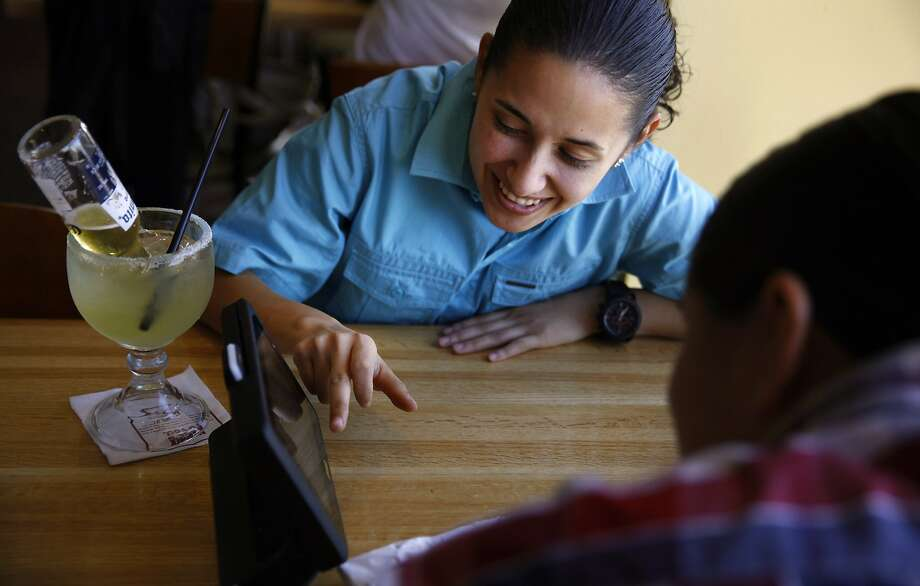 Gloria Garcia (left) and Carina Arteaga of Livingston (Merced County), play a game on a tablet at the Applebee's at Fisherman's Wharf in San Francisco. Restaurants are beginning to incorporate the devices into the dining experience. Photo: Nicole Fruge, The Chronicle