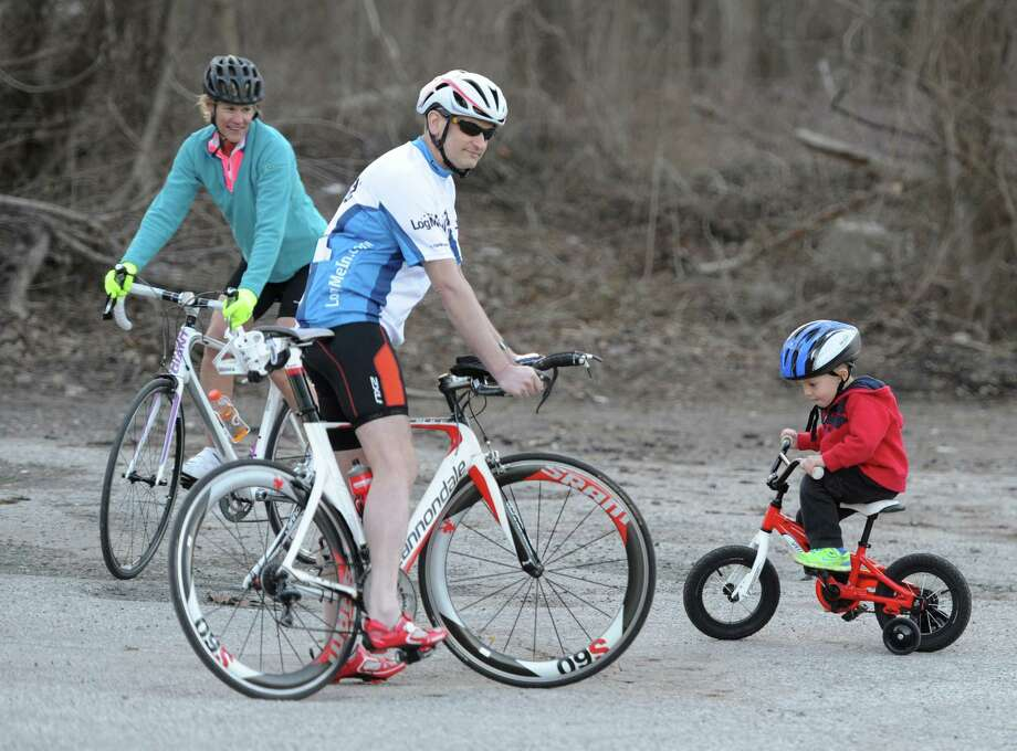 Debbie Heelan, of Bethel, and Bill Baker, of New Milford, ride their bikes as Jack Pierz, 3, of Brookfield, rides a tricycle outside Woodbridge Running Company in Brookfield, Conn. Wednesday, April 9, 2014. Photo: Tyler Sizemore / The News-Times