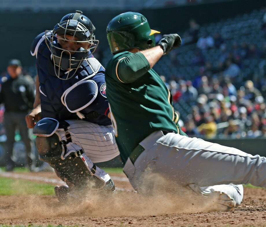 Minnesota Twins catcher Josmil Pinto, left, tags out Oakland A's Jed Lowrie as he tried to score, at Target Field in Minneapolis, Thursday, April 10, 2014. Photo: Bruce Bisping, McClatchy-Tribune News Service