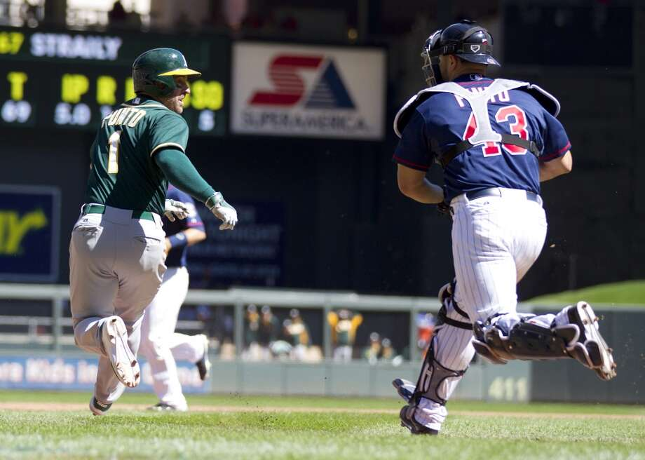 Oakland Athletics third baseman Nick Punto (1) is chased by Minnesota Twins catcher Josmil Pinto (43) in the sixth inning of their baseball game on Thursday, April 10, 2014 in Minneapolis. The Athletics beat the Twins 6-1. Photo: ANDY CLAYTON-KING, Associated Press