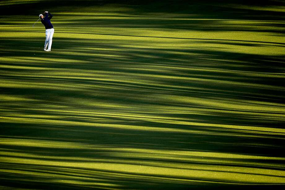 Shadows on the fairway: Stewart Cink hits his second shot on the second hole at the Masters in Augusta, Ga. Photo: Harry How, Getty Images