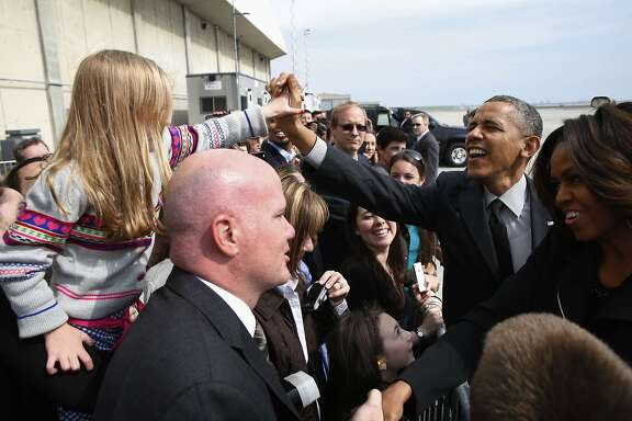 U.S. President Barack Obama and first lady Michelle Obama (R) greet well-wishers upon their arrival at JFK Airport in New York April 11, 2014. President Obama is in New York to speak at the National Action Network's 16th Annual Convention. REUTERS/Kevin Lamarque (UNITED STATES - Tags: POLITICS)