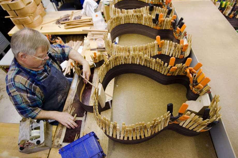 David Anthony installs a ribbon  lining of a guitar on the factory floor of C. F. Martin & Co.,  in  Nazareth,  Pa. (AP Photo/Matt Rourke)