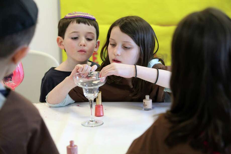 Harry Cohan, 6,  watches his sister Sofia, 7, paint a cup for Passover during a Model Matzah Bakery event at Chabad of Fairfield on Sunday, April 6, 2014. Children learn how to make handmade Passover Matzah at the event. Photo: BK Angeletti, B.K. Angeletti / Connecticut Post freelance B.K. Angeletti