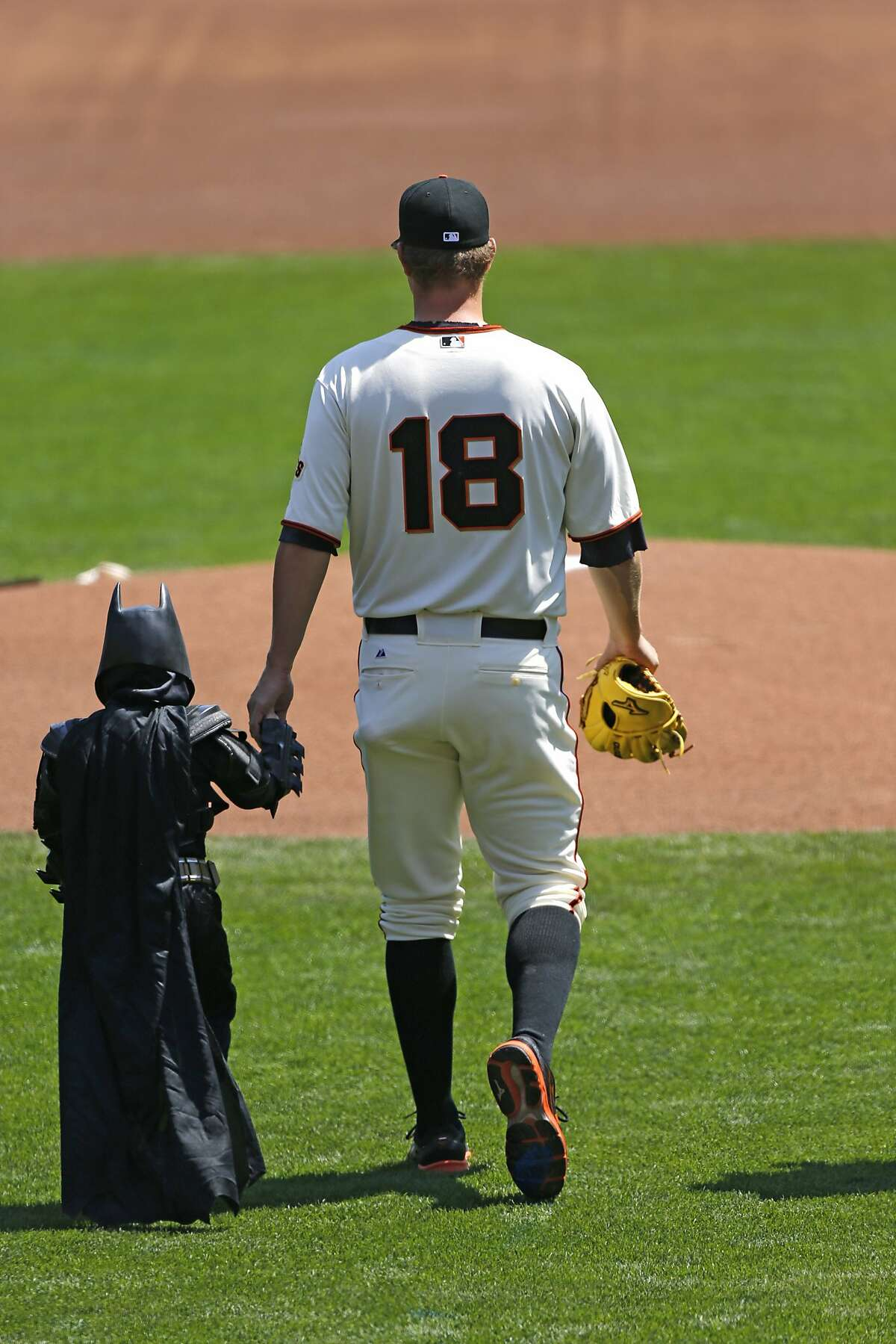 Giants pitcher Matt Cain walks Batkid to the pitcher's mound during the opening ceremonies as the San Francisco Giants prepare to take on the Arizona Diamondback during their home opener at AT&T Park on Tuesday April 8, 2014, in San Francisco, Calif.