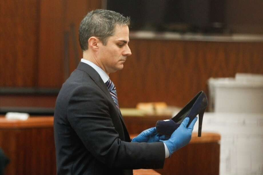 Prosecutor John Jordan shows the bloody shoe to the jury during the trial against Ana Lilia Trujillo on Tuesday, April 1, 2014, in Houston.