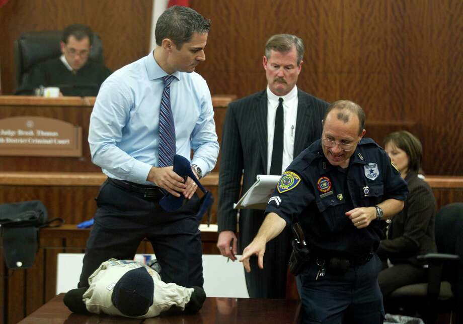 Prosecutor John Jordan does a crime scene demonstration with Houston Police senior officer Christopher Duncan, using a dummy, during the trial on Tuesday, April 1, 2014. Photo: Brett Coomer, Houston Chronicle / © 2014 Houston Chronicle