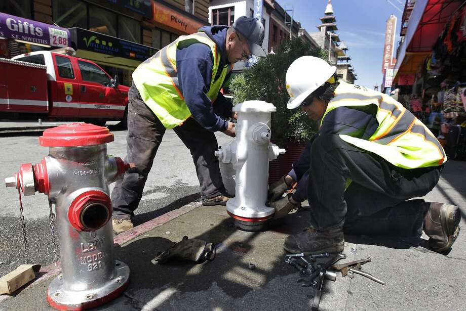 Mike Hara (left) and Russell Yuen replaces a damaged fire hydrant (left) with a new one at Grant Avenue and Pine Street in San Francisco, Calif. on Wednesday, April 9, 2014. Vandals have been illegally repainting hydrants across the city, forcing utility workers to remove and replace them at a high cost. Photo: Paul Chinn, The Chronicle