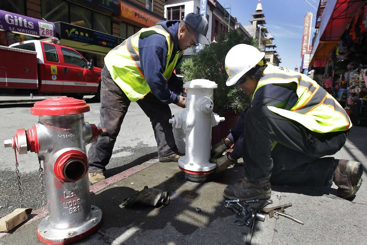 Mike Hara (left) and Russell Yuen replaces a damaged fire hydrant (left) with a new one at Grant Avenue and Pine Street in San Francisco, Calif. on Wednesday, April 9, 2014. Vandals have been illegally repainting hydrants across the city, forcing utility workers to remove and replace them at a high cost.