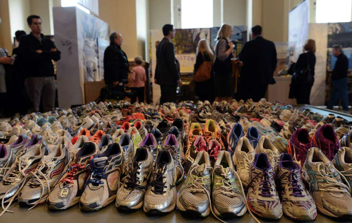 """People attend the Boston Marathon memorial exhibition, """"Dear Boston: Messages from the Marathon Memorial,"""" at the Boston Public Library last week."""
