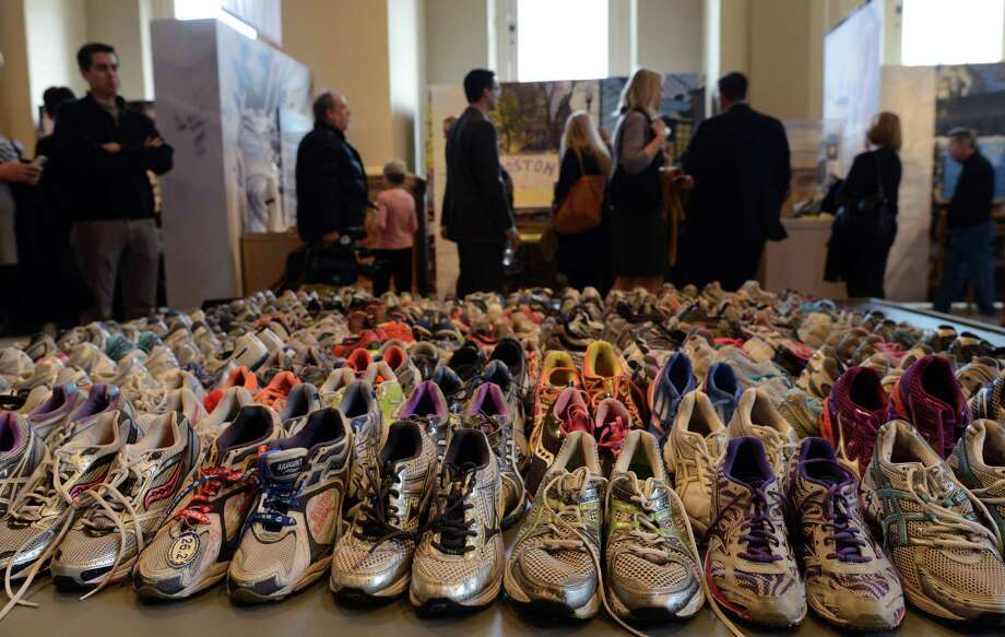 "People attend the Boston Marathon memorial exhibition, ""Dear Boston: Messages from the Marathon Memorial,"" at the Boston Public Library last week. Photo: Darren McCollester / Getty Images / 2014 Getty Images"