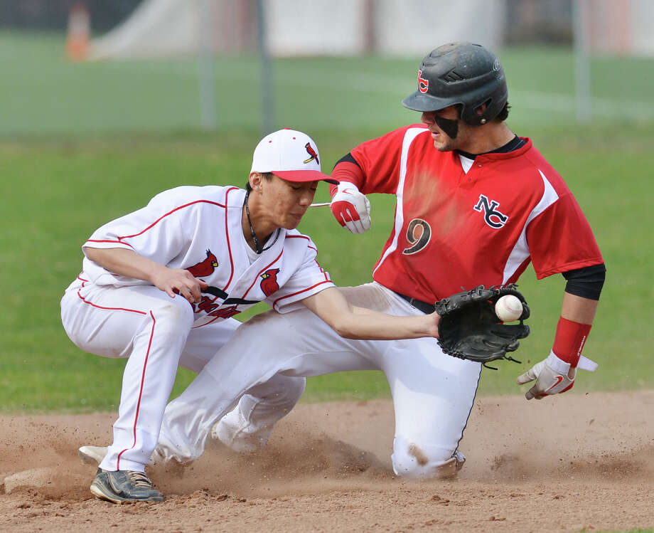 At left, Greenwich shortstop Keigo Fujikura takes the throw but New Canaan's Nick Cascione is safe at second on a steal during the high school baseball game between Greenwich High School and New Canaan High School at Greenwich, Friday afternoon, April 11, 2014. Photo: Bob Luckey / Greenwich Time