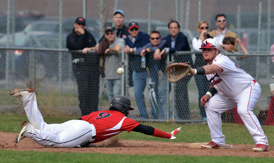 New Canaan's Nick Cascione, left, gets back to first safely on a pickoff attempt as Greenwich first baseman Justin Gaccione takes the throw during the high school baseball game between Greenwich High School and New Canaan High School at Greenwich, Friday afternoon, April 11, 2014. Photo: Bob Luckey / Greenwich Time