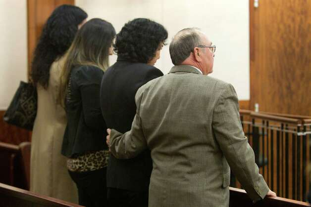 Russell Tharp, far right, puts his arm around his wife, Maria, Ana Trujillo's mother, as Trujillo is sentenced to life in prison for killing her boyfriend with the heel of a stiletto shoe Friday, April 11, 2014, in Houston. Trujillo was convicted in the brutal 2013 slaying of her boyfriend, Alf Stefan Andersson, using a 5-inch stiletto shoe. Photo: Brett Coomer, Houston Chronicle / © 2014 Houston Chronicle