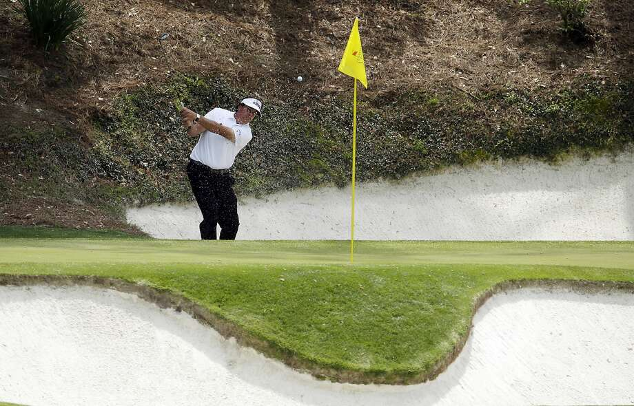 Phil Mickelson hits out of a bunker on No. 12, where he posted a triple bogey. The hole inflated his second-round score to 73 and he missed the Masters cut for the first time since 1997. Photo: Charlie Riedel, Associated Press