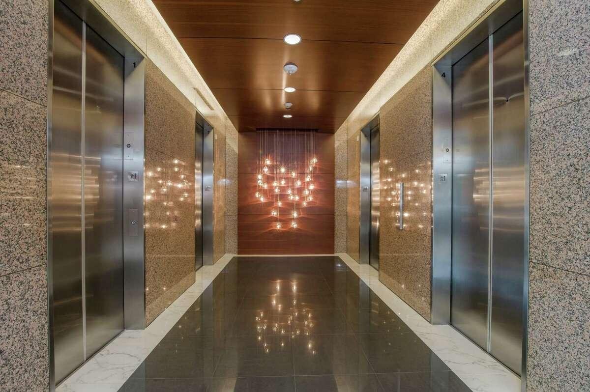 Renovation of the lobby at Loop Central Three included new elevator cab interiors. The building is owned by TIER REIT. Photographs of the 4828 Loop Central property for marketing and advertising