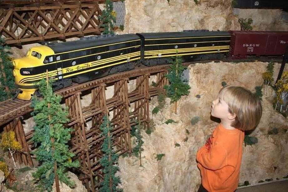 "Asher Larkin Murray enjoys watching a train cross the trestle bridge from a ""G scale"" model train layout. Photo: Courtesy Rosenberg Railroad Museum"