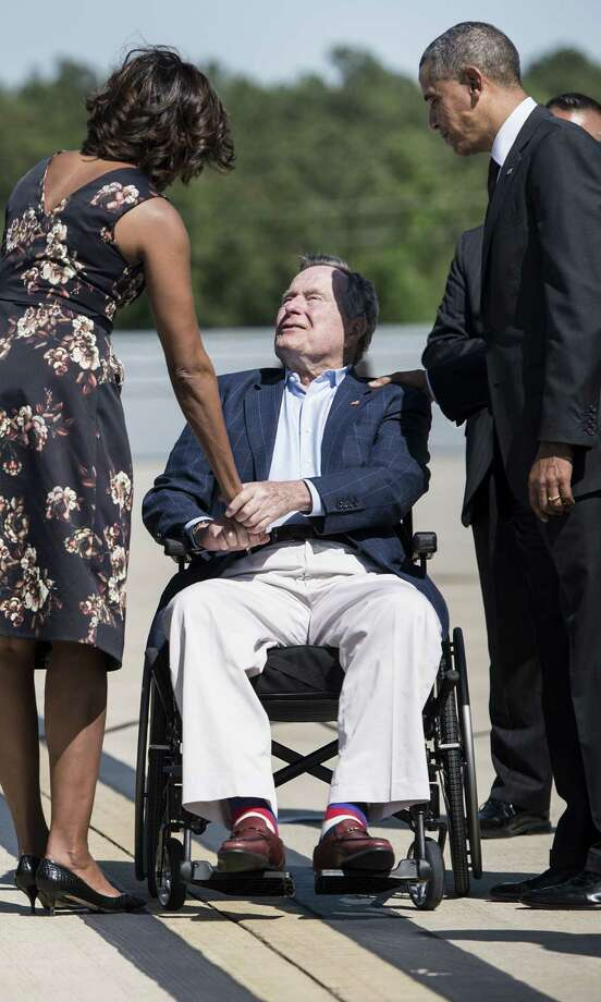 Former US President George H. W. Bush greets President Barack Obama and First Lady Michelle Obama as they arrive at Intercontinental Airport on April 9, 2014 in Houston, Texas. AFP PHOTO/Brendan SMIALOWSKIBRENDAN SMIALOWSKI/AFP/Getty Images Photo: BRENDAN SMIALOWSKI, Staff / 2014 Brendan Smialowski