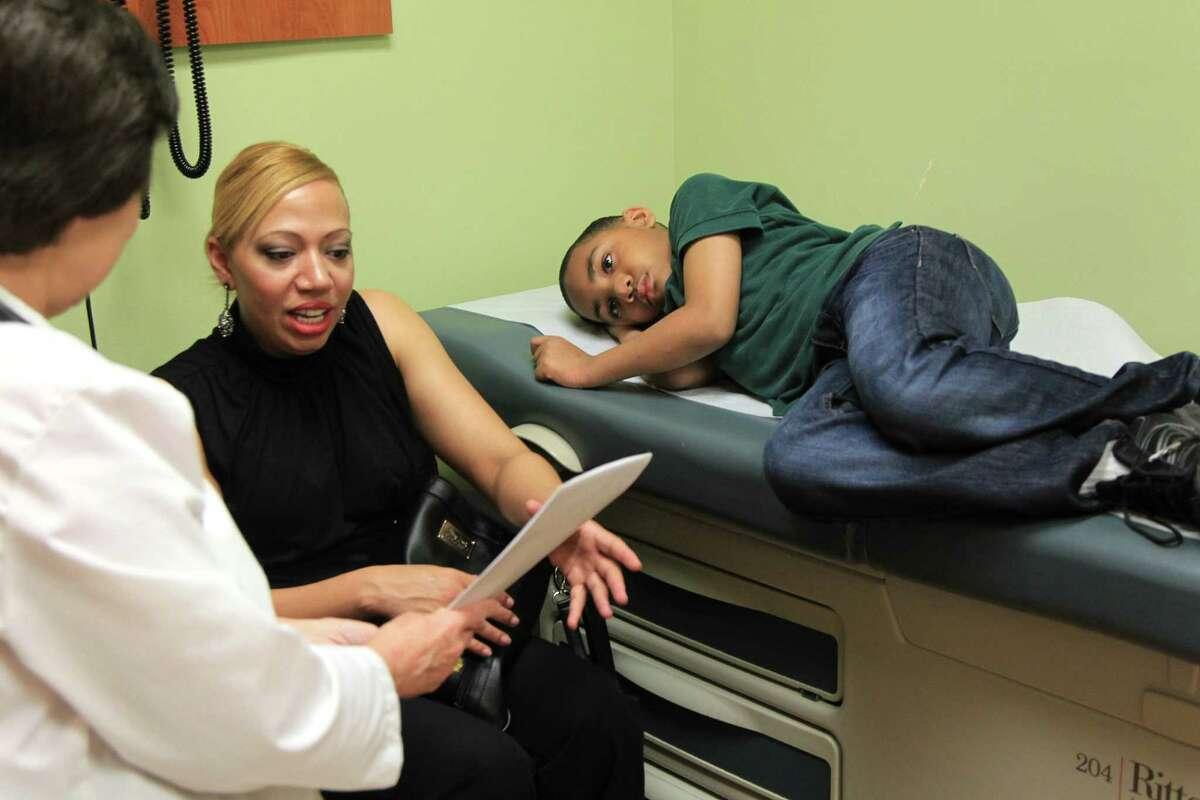 Audreyanna Pratt receives instructions from a nurse practitioner about son Xavier Ogunbufunmi.